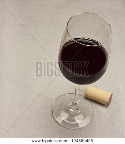 A glass of red wine with a cork on a grey textile texture with copyspace