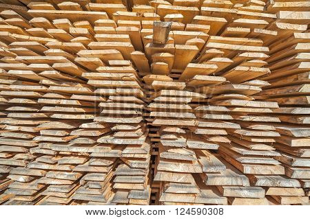 Stack of rough wooden boards in lumberyard.