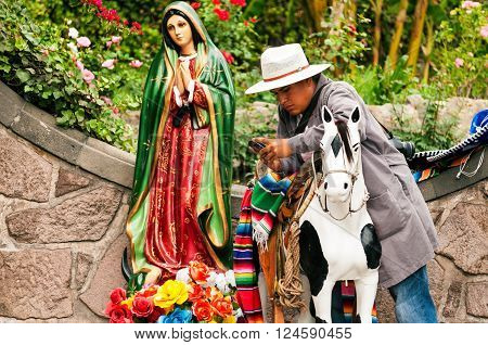 MEXICO CITY - MARCH 30: Man with cellphone next to religious statue in Mexico City on March 30 2013