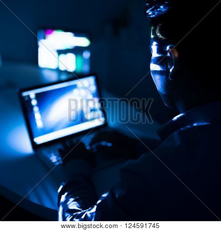 Programmer computing at night, view over the shoulder