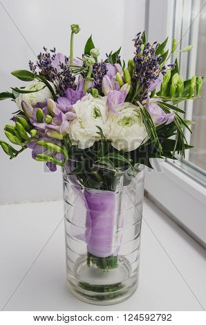 Beautiful spring bouquet of wedding flowers buttercup ranunculus, fresia, lavender in vase with violet tape. Pastel colors purple, green. Rustic style, still life. Holiday wedding floristic, bouquet of bride. Marriage. White Background.