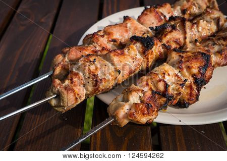 Cooking kebabs on the grill. Plate with meat on wooden table.