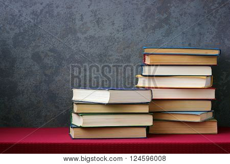 Books with colored covers on the table with a red tablecloth on the old grey wall background with texture.