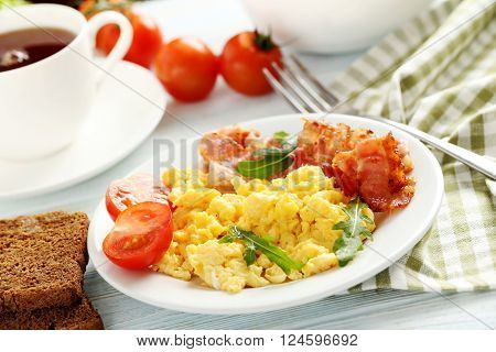 Scrambled Eggs With Bacon And Vegetables On A Blue Wooden Table