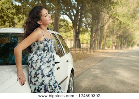 girl stand on country road near car, big high trees, summer season