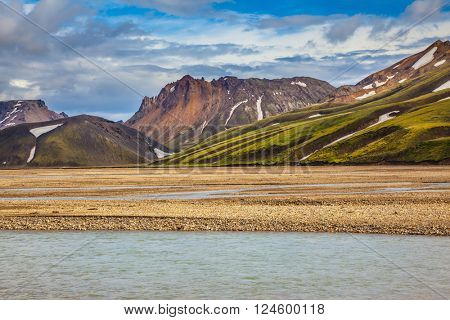 The magic of summer in Iceland. Cold water streams among yellow tundra. Landmannalaugar National Park