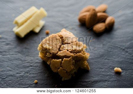 White chocolate and almond brownie on dark background. White chocolade whole almonds and crumbles. Selective focus.