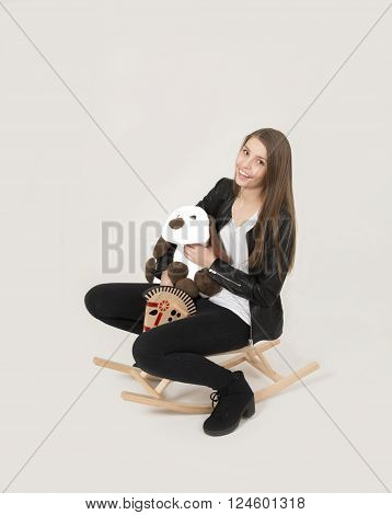 Teenage girl with cute soft toy riding a rocking horse ** Note: Soft Focus at 100%, best at smaller sizes