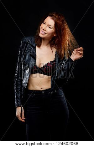 Young attractive woman wearing black leather jacket over her bra, shoot over black background