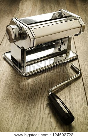 Metal reflective pasta machine with separated hand crank wood surface. Selective focus on pasta machine.