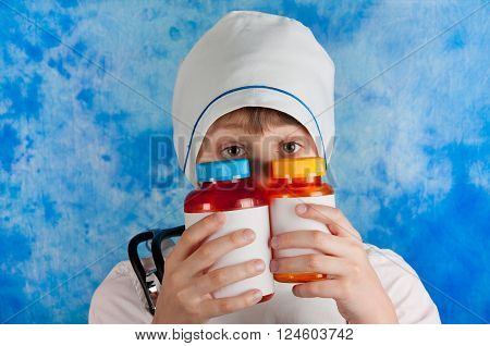 Boy in white doctor's costume and cap looking out two bottles for pills