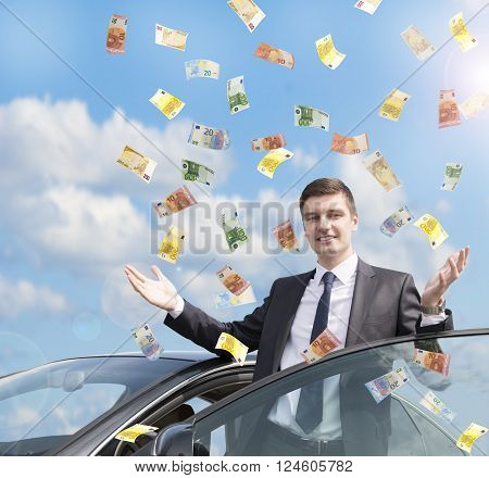 Happy businessman standing near his car in the rain of euro money.  Euro are falling from the sky