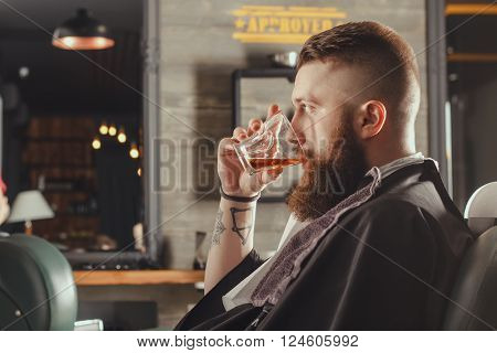 Serious Young Bearded Man Sitting In Chair At Barbershop  And Drinking Whiskey From A Glass . Barbershop Theme