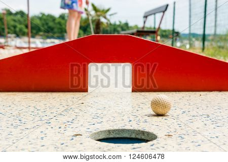 Mini golf, closeup of red gates. Ball moving towards hole.