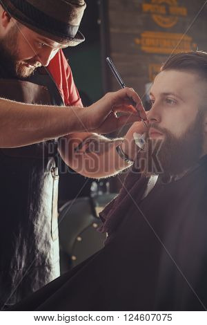 Young Bearded Man Getting Beard Haircut With A Straight Razor By Barber. Barbershop Theme