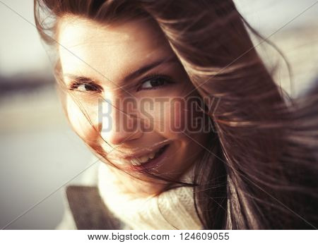 Windy portrait of attractive young woman with a cheerful toothy smile. The model showing friendly facial expression and her hair looks beautiful