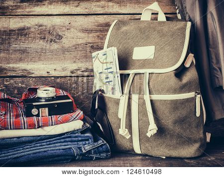 Travel backpack,  clothing, map, filmstrip and retro film camera. Vintage stylized.
