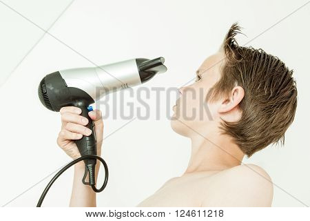 Young Boy Blowing His Hair Dry With A Hairdryer