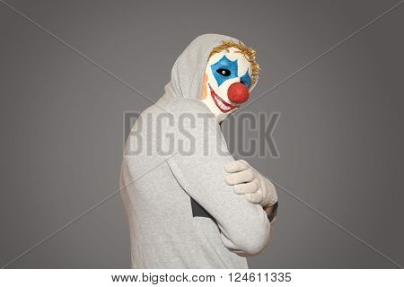 masked man evil clown stands sideways on a gray background