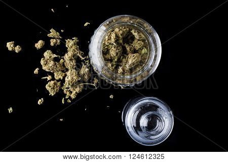 Medical cannabis buds in an open glass jar with marijuana flowers scattered aside and transparent lid on black background directly from above