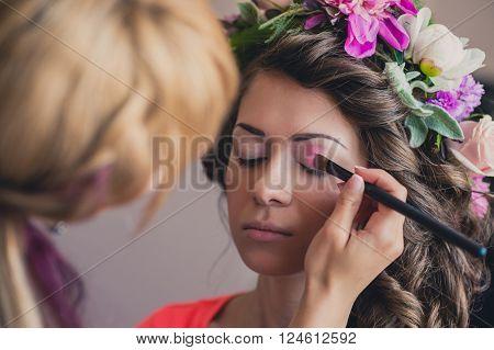 The visagist is applying wedding makeup. The bride closed her eyes.