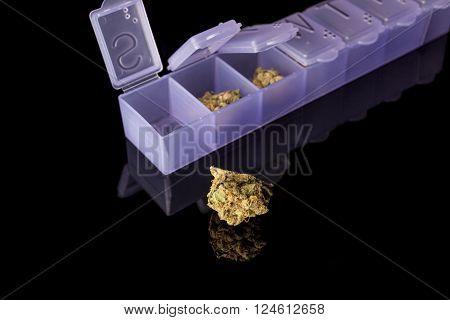 Marijuana buds in dosage plastic purple drugs container on black background from side