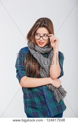 Pensive casual woman in glases looking away isolated on a white background