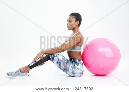 Gorgeous beautiful young african american sportswoman sitting and posing with fitball over white background