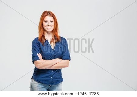 Cheerful pretty redhead young woman standing with hands folded over white background