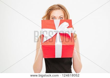 Cute lovely young woman hiding her face behing present box over white background