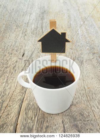 White cup of coffee with blank blackboard house shape on wooden background