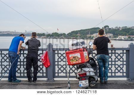 Istanbul Turkey - Jun 28 2015: Three men were fishing facing Bosphorus Strait in early morning on Galata Bridge. A motorcycle for fastfood delivery was between them.