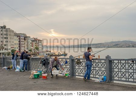 Istanbul Turkey - Jun 28 2015: Four men were fishing facing Bosphorus Strait when sunlight just broke clouds in early morning on Galata Bridge. One man was also selling fishing gears.