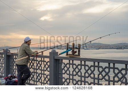 Istanbul Turkey - Jun 28 2015: A man wearing cap was leaning beside three fishing rods on railing of Galata Bridge facing Bosphorus Strait in early morning before sun came out from dense clouds.