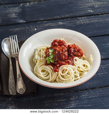 Spaghetti and meatballs in tomato sauce in a ceramic saucer on dark wooden background. Delicious food