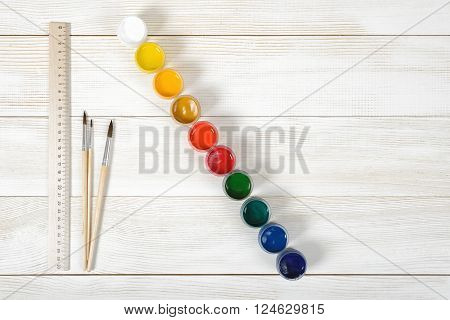 Top view of two paint brushes and a centimeter ruler with colorful gouache containers on a light wooden background.
