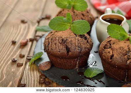 Chocolate muffins with mint on a brown background