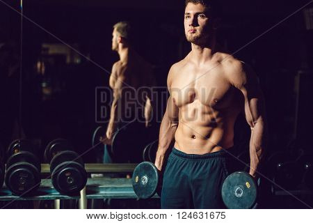 Very power athletic guy bodybuilder , execute exercise with dumbbells