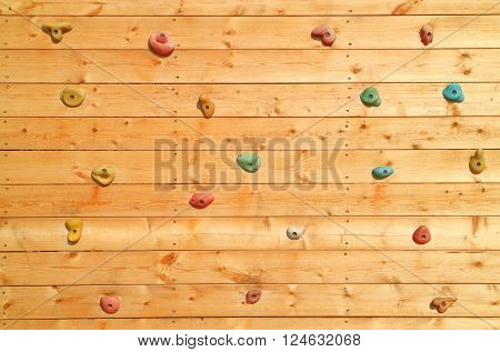 The wood surface of an artificial rock climbing wall with hand and toe hold studs adventure and extreme sport activity.