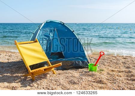 Blue shelter and yellow chair at the beach