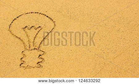 Light bulb drawn by hand on the beach sand.
