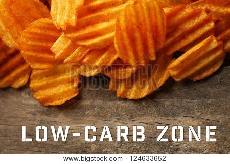 Text Low-Carb Zone and potato chips on wooden background
