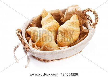 Fresh homemade croissants in basket. Isolated on white background