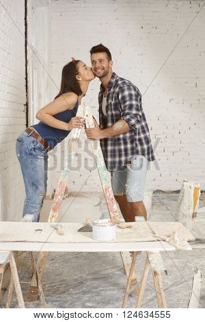 Happy young couple kissing on ladder at home renewal.