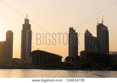 cityscape, travel, tourism and urban concept - Dubai city business district skyscrapers and seafront at evening