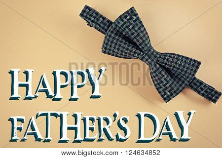 Happy Father's Day. Male bow tie on beige background