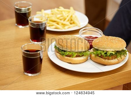 fast food, unhealthy eating and junk-food concept - close up of hamburgers, drinks and french fries on table at home