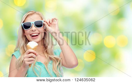 summer, junk food and people concept - young woman or teenage girl in sunglasses eating ice cream over summer green lights background