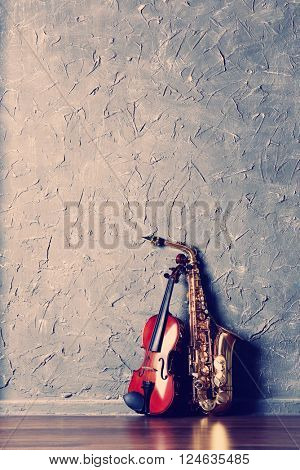 Violin and saxophone on gray wall background