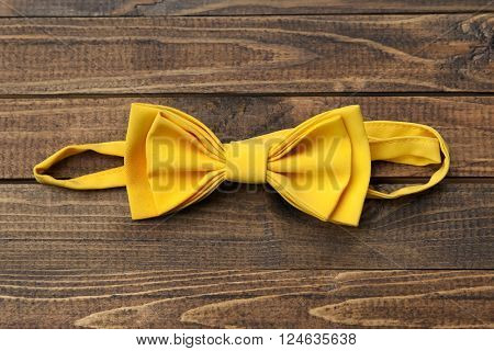 yellow bow tie on a wooden background